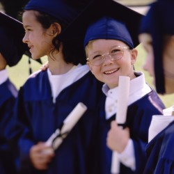 Children dressed in graduation outfits holding diplomas