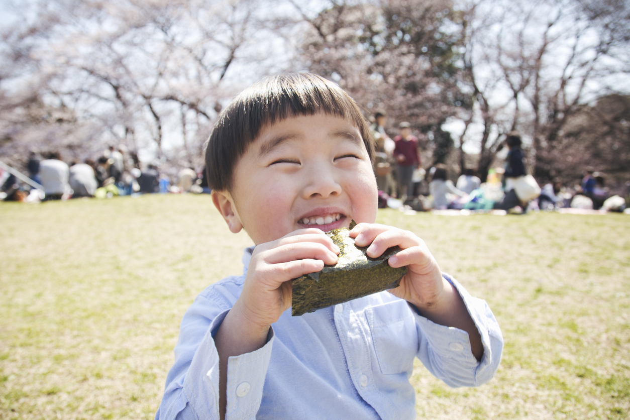 Boy eating a rice bowl in the park