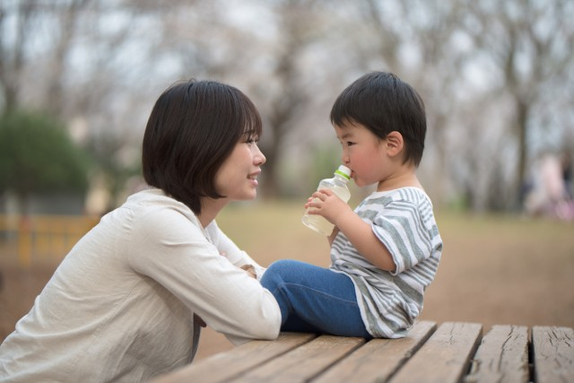 Mother and child sitting on bench and talking