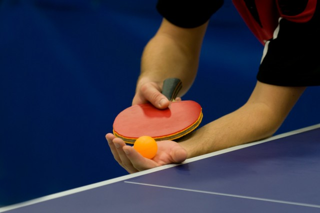 Mans hands about to serve a game of table tennis