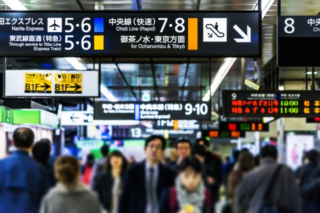 passengers walk in shinjuku station and focus on traffic sign board in tokyo, shinjuku.