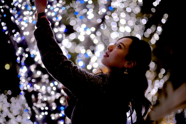 Young woman standing before Christmas illuminations
