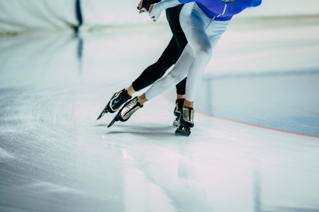 feet man athletes skater on ice go ice Palace of sports. competitions indoors. warm-up
