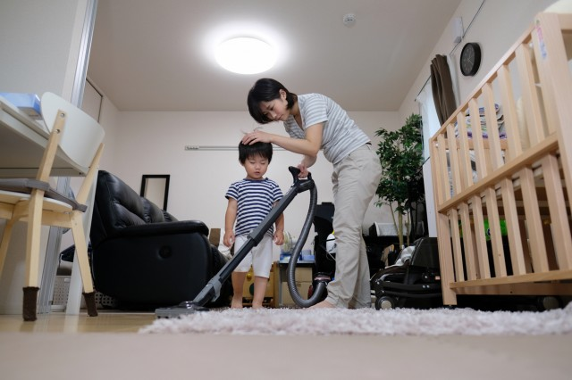 housewife vacuuming room with child