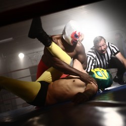 Referee watches as two masked wrestlers fight