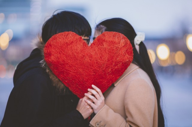 Couple Hiding Behing Heart Shape And Kissing Each Other