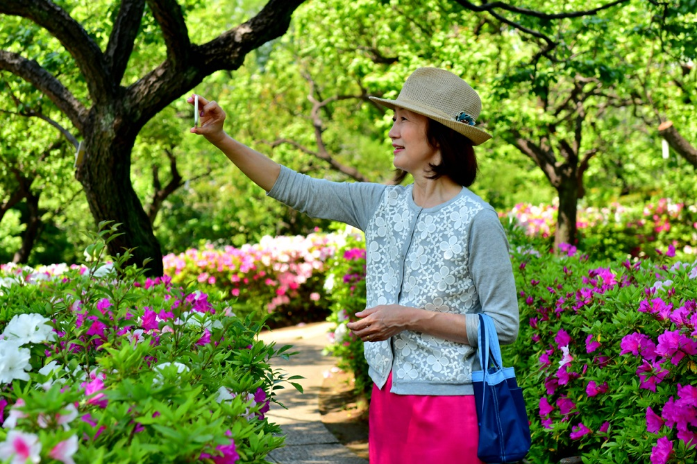 Japanese Woman Taking Selfie in Park with Azalea in Full Bloom