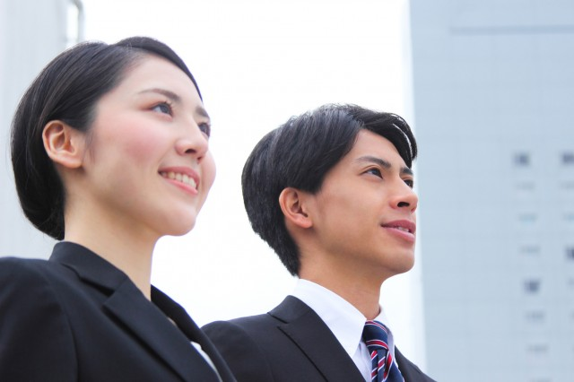 Asian businessman and businesswoman looking up at the sky