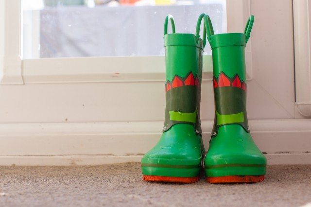 Young childrens colorful wellies sat on a mat by the back door