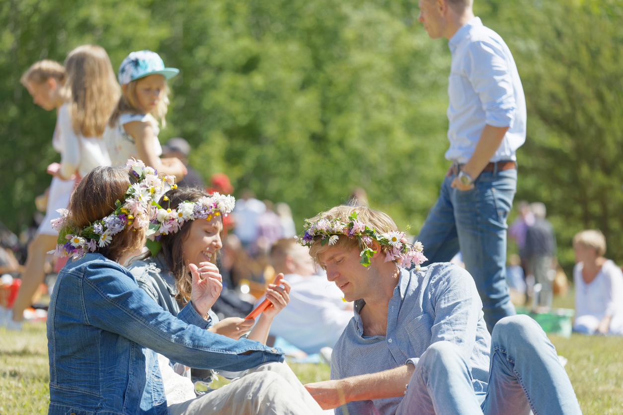 Two woman and a man with flower in their hair having a pic-nic sitting in the grass before celebrating the Midsummer in Sweden