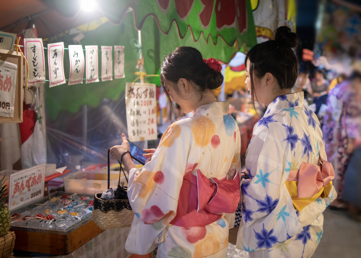 Young female friends in yukata shopping at Japanese Yatai market in festival