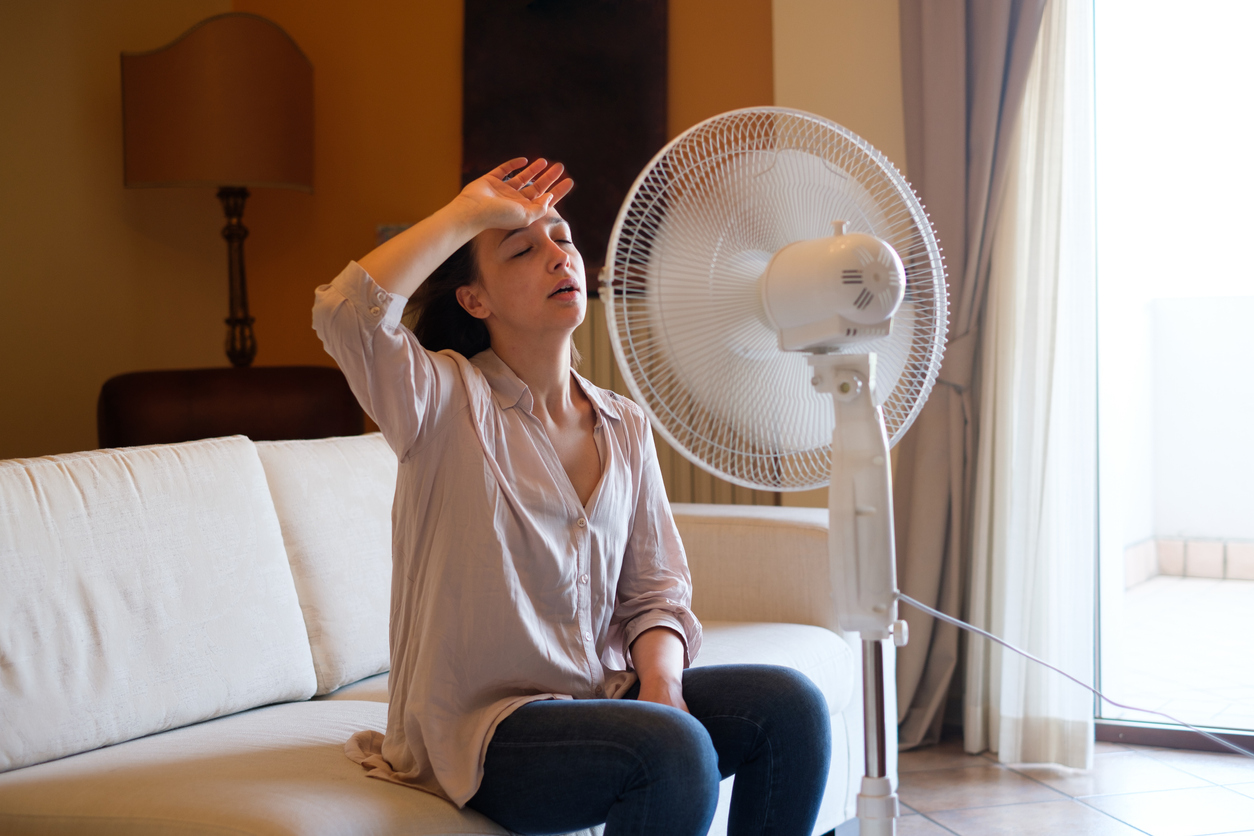 Young woman relaxing under the air fan at home