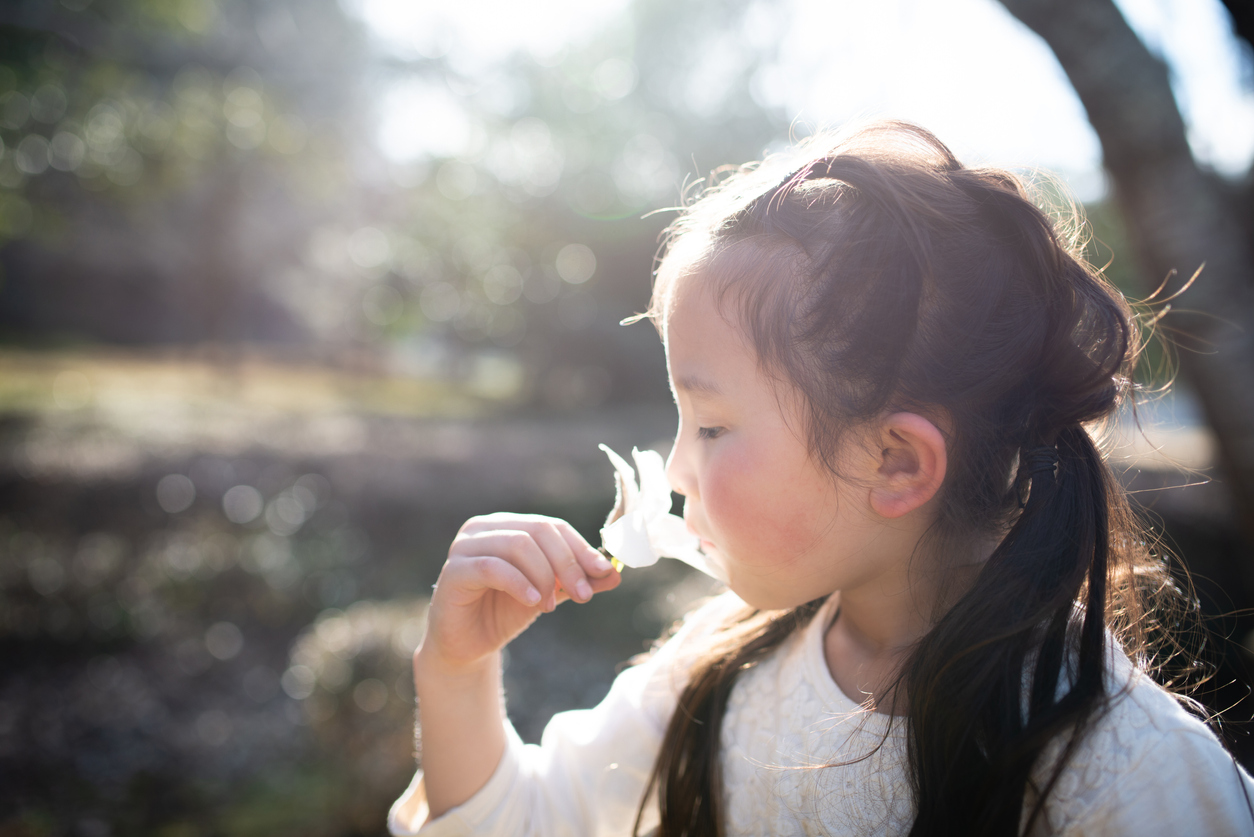 Girl smelling the smell of white flower