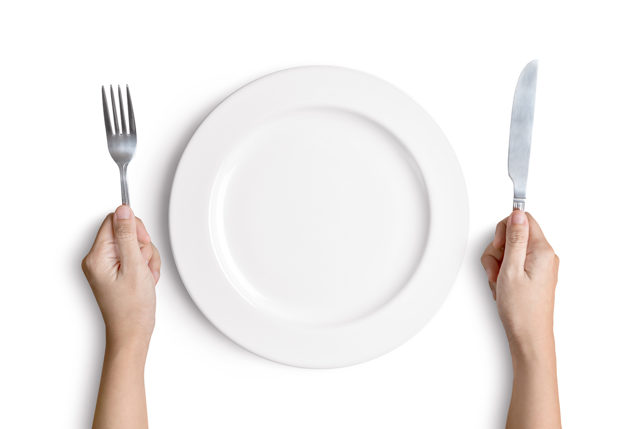 White plate with silver fork and spoon