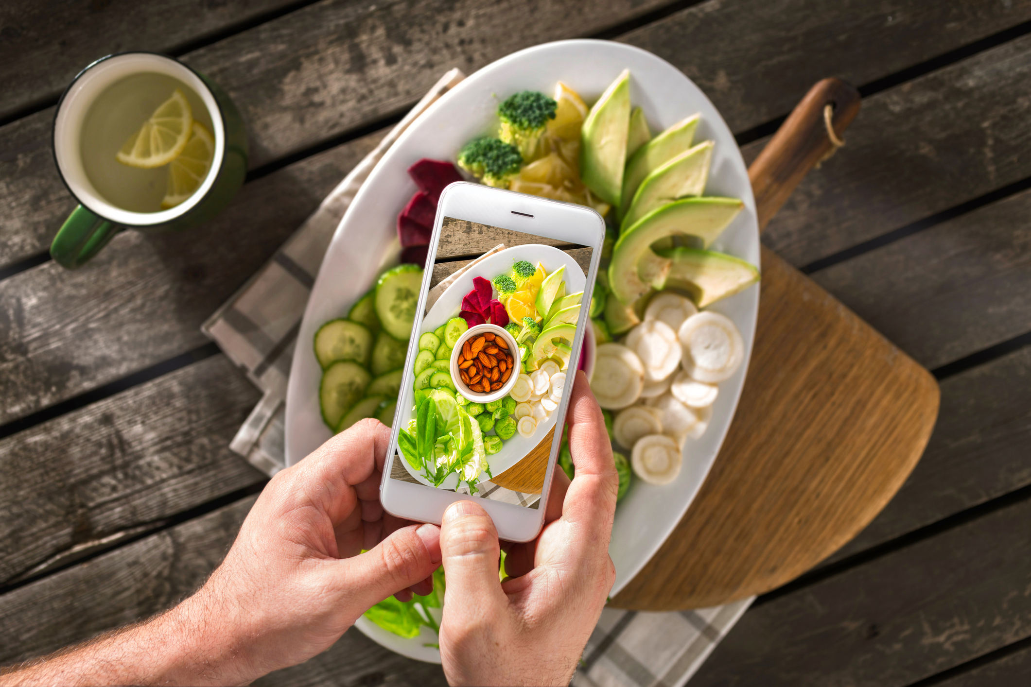 Food photography on phone. Food blogging content concept. Male hands take photo of vegan plate with screen phone
